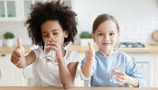 Two kids giving thumbs up to purified water