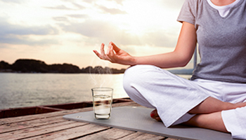 A person meditating with a glass of purified water