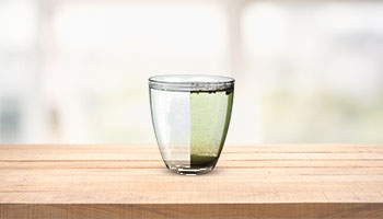 A glass with half purified water and half dirty water on a wooden table